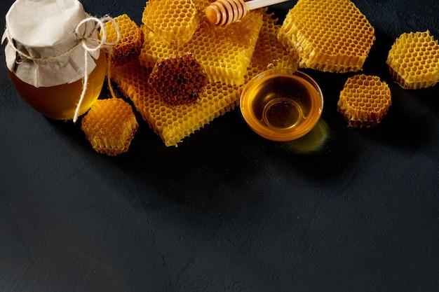 Pot De Miel Avec Nid D'abeille Sur Table Noire, Vue Du Dessus. Espace Pour Le Texte. Photo Premium