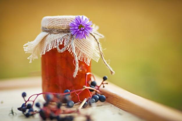 Pot en verre avec une délicieuse confiture d'abricot sur une table. temps de l'automne Photo Premium