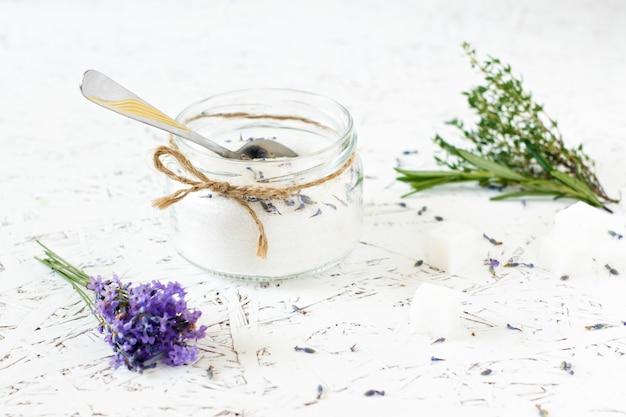 Pot en verre avec du sucre de lavande, de la lavande fraîche sur un fond en bois clair Photo Premium