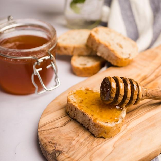 Pot en verre plein de miel avec une cuillère à miel Photo gratuit