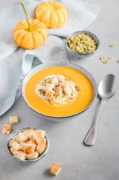 Potage à La Citrouille Avec Crème, Croûtons, Graines De Citrouille Et Thym Sur Béton Gris Ou Pierre Photo Premium