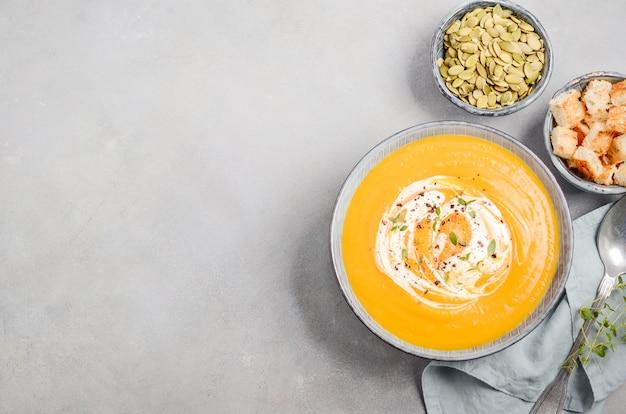 Potage à La Citrouille Avec Crème, Croûtons, Graines De Citrouille Et Thym Photo Premium