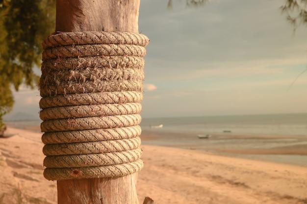 Poteau en bois avec cordes d'amarrage sur la plage. Photo Premium
