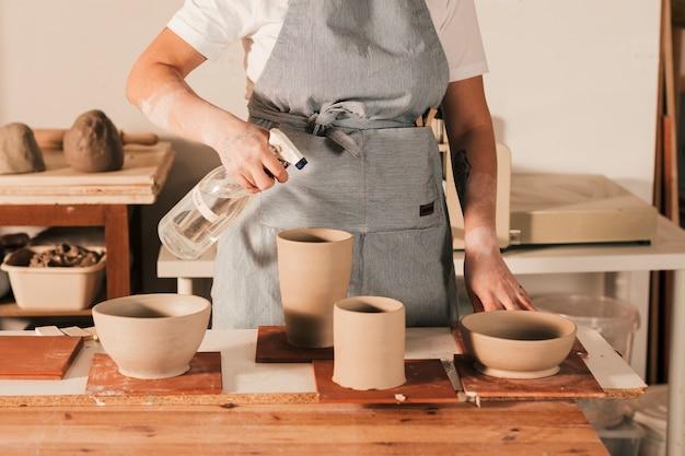 Potier féminin pulvériser le liquide sur des bols d'argile à la main et pot sur table en bois Photo gratuit