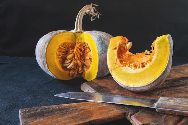 Potiron aux légumes coupé en deux sur une planche à découper en bois Photo Premium