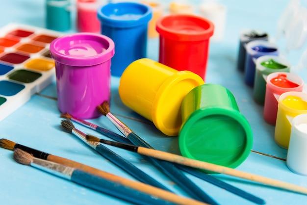 Pots Colorés Avec Gouache Et Aquarelles Sur Fond Bleu. Photo Premium