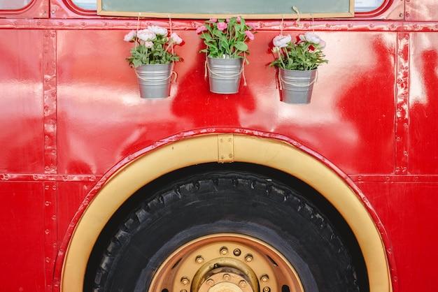 Pots avec des plantes de décoration suspendus à un bus rouge dans une exposition de voitures anciennes. Photo Premium