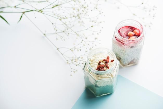 Pots de smoothie sains et gypsophile sur fond blanc Photo gratuit