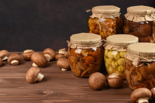 Pots Avec Une Variété De Champignons. Champignons Marinés En Conserve Dans Des Bocaux En Verre. Champignons Confits Sur Table En Bois. Photo Premium