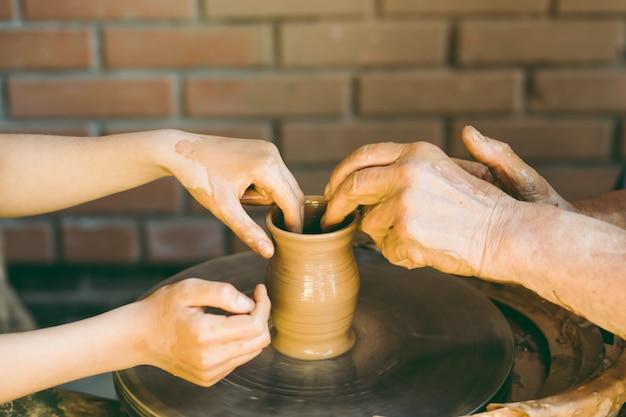 Potter apprend à sculpter un pot en argile Photo Premium