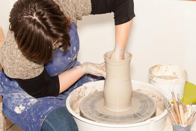 Potter Femelle Créant Un Pot En Terre Sur La Roue D'un Potier Photo Premium