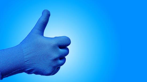Le pouce vers le haut le geste de la main dans le gant isolé sur fond bleu Photo Premium