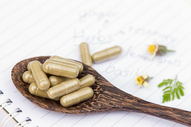 Poudre à base de plantes avec des capsules pour une alimentation saine à partir de nombreuses herbes Photo Premium