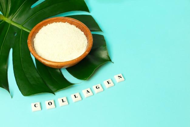 Poudre de collagène dans un bol et mot collagen sur une feuille de palmier Photo Premium