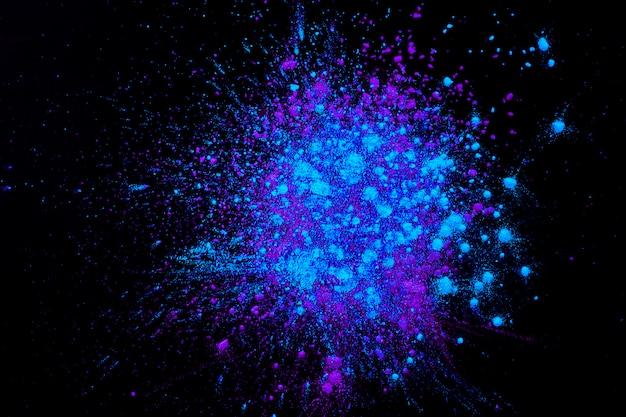 Poudre colorée mélangée sur une surface sombre Photo gratuit