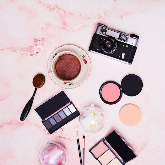 Poudre compacte pour le visage; ruban; tasse à café; pinceau de maquillage; palette fard à paupières et appareil photo vintage sur fond texturé rose Photo gratuit