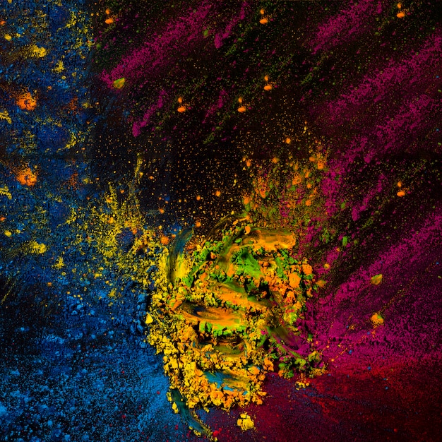Poudre de holi abstraite tachée sur une surface noire Photo gratuit