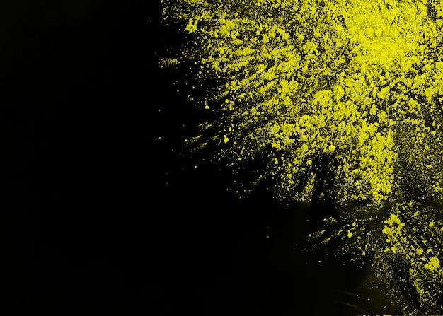 Poudre de holi jaune sur le coin de la surface noire Photo gratuit