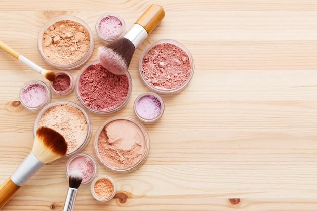 Poudre de maquillage et pinceaux sur fond de bois Photo Premium