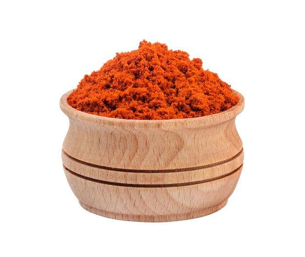 Poudre de paprika rouge dans un bol en bois isolé sur fond blanc Photo Premium