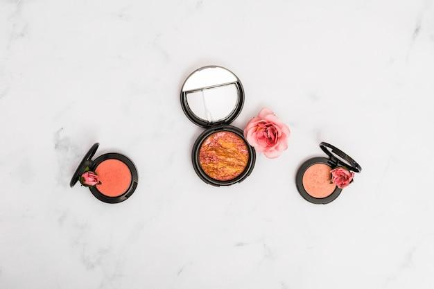 Poudre pour le visage compacte avec rose et boutons sur fond de marbre texturé Photo gratuit