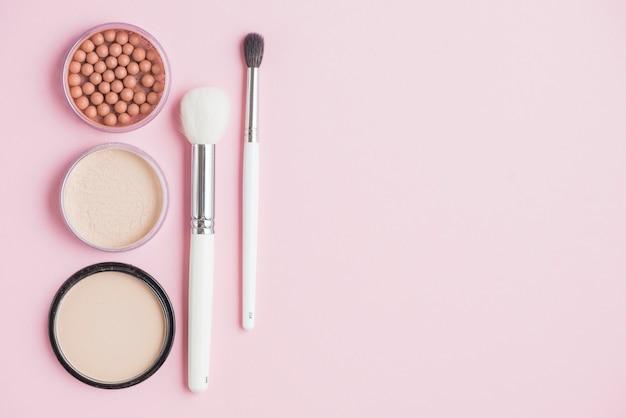 Poudres compactes; perles de bronzage et pinceaux de maquillage sur fond rose Photo gratuit