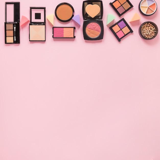 Poudres pour le visage avec ombres à paupières sur table rose Photo gratuit