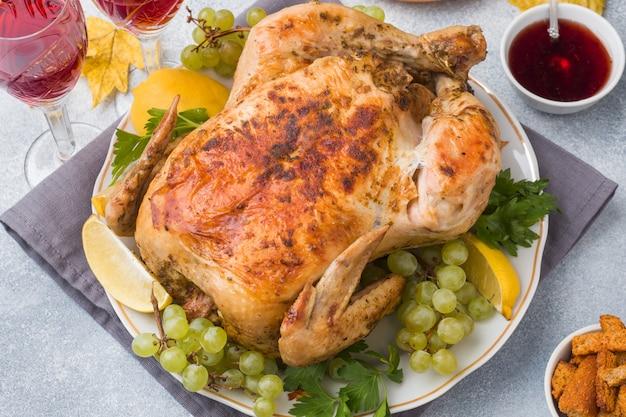 Poulet au four, purée de pommes de terre et verres à vin pour le dîner sur la table de fête. Photo Premium