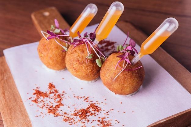 Poulet biryani arancini servi dans une boule de riz avec une trempette sucrée et épicée. Photo Premium