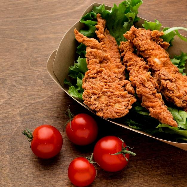 Poulet Frit à Angle élevé Avec Salade Et Tomates Photo gratuit