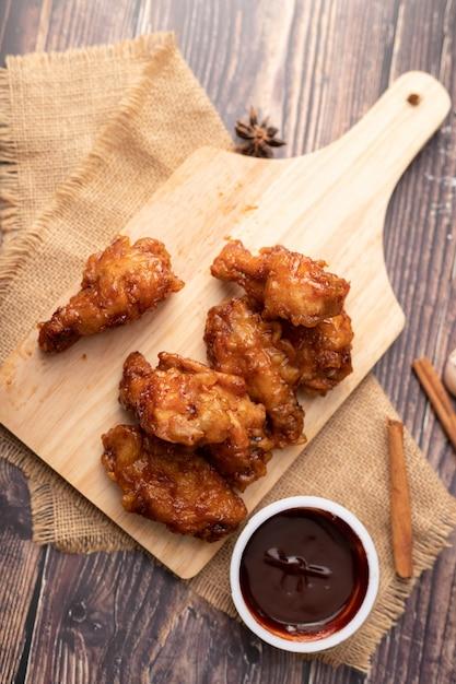 Poulet frit au barbecue coréen chaud et épicé sur une planche à découper en bois Photo Premium