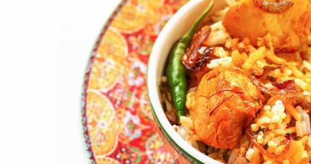 Poulet indien biryani servi avec fond blanc raita yaourt, tomate. mise au point sélective. Photo Premium