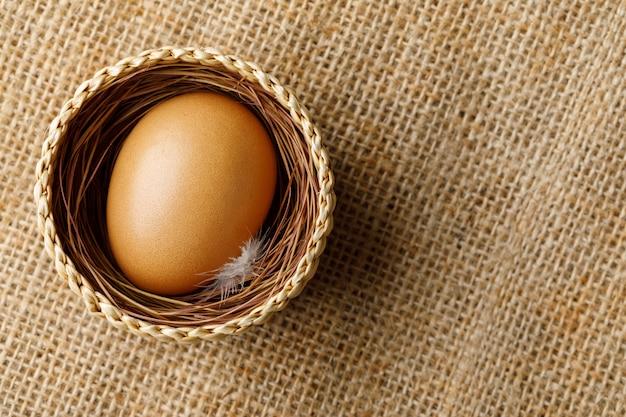 Poulet ou œuf de poule dans un panier en osier sur un sac Photo Premium