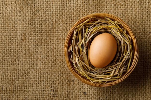 Poulet ou œuf de poule sur paille dans un panier en osier sur un sac Photo Premium