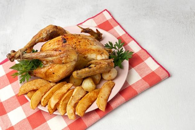 Poulet rôti appétissant avec pommes de terre à l'ail et oignons Photo Premium