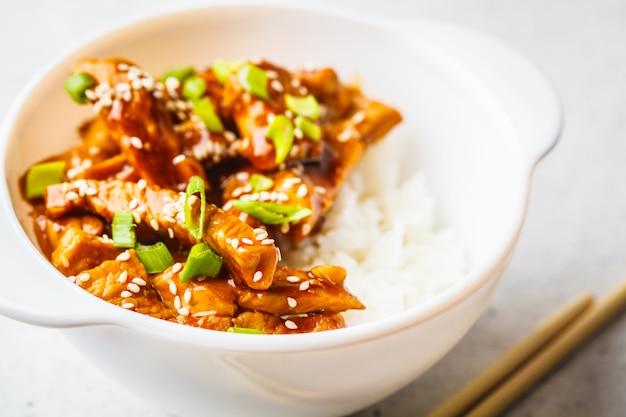 Poulet Teriyaki Asiatique Avec Riz, Sésame Et Oignons Verts Dans Un Bol Blanc. Photo Premium