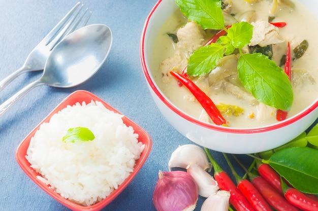 Poulet vert au curry avec ingrédient épicé cru et riz avec une cuillère et une fourchette Photo gratuit