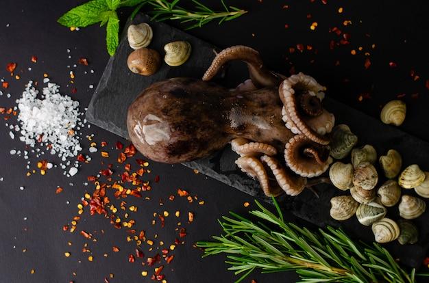 Poulpe cru frais aux palourdes et ingrédients pour la cuisson sur ardoise noire sur fond sombre Photo Premium