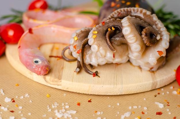 Poulpe cru et poisson prêt pour la cuisson sur une planche à découper en bois avec espace de copie Photo Premium