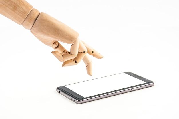 Poupée de main en bois touchant un téléphone intelligent sur fond blanc Photo Premium