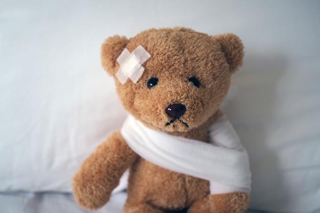 Poupée ours triste malade au lit avec la plaie à la tête et un bandage Photo Premium