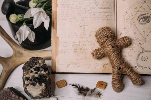 Une Poupée Vaudou En Corde Se Trouve Avec Un Vieux Livre Grimoire Photo Premium
