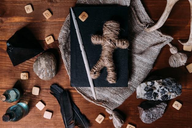 Une Poupée Vaudou Faite De Corde Se Trouve Sur Un Livre Noir, Entouré D'objets Rituels Magiques, Mise à Plat Photo Premium