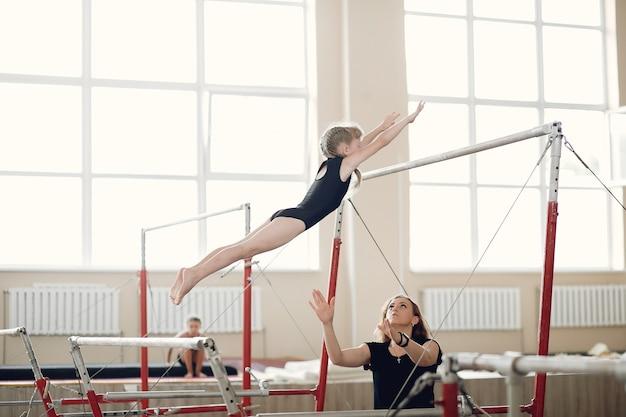 Poutre De Gymnastique Enfant. Athlète Gymnaste Fille Lors D'un Exercice Barre Horizontale Dans Les Compétitions De Gymnastique. Coach Avec Enfant. Photo gratuit