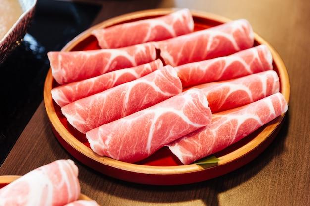 Premium rare slices porc kurobuta (porc noir) à texture marbrée élevée sur une assiette en bois en forme de cercle. Photo Premium