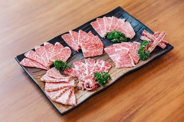 Premium rare tranches de nombreuses parties de bœuf wagyu à la texture marbrée élevée sur une assiette en pierre, servies pour yakiniku, viande grillée .. Photo Premium