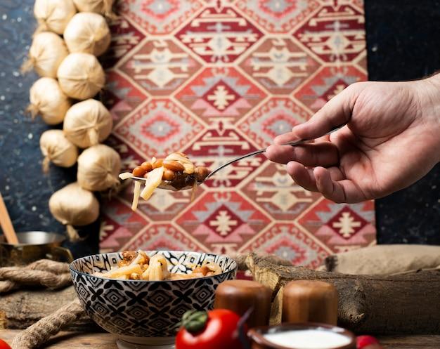 Prendre des nouilles de haricots dans un bol avec une cuillère. décoration de style ethnique. Photo gratuit
