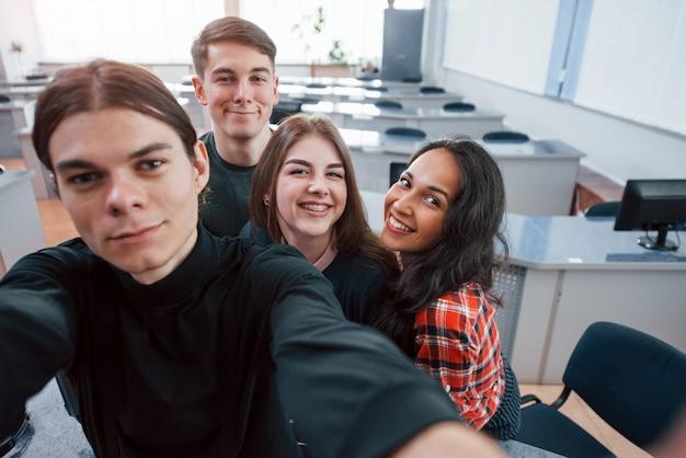 Prendre Un Selfie. Groupe De Jeunes En Vêtements Décontractés Travaillant Dans Le Bureau Moderne Photo gratuit