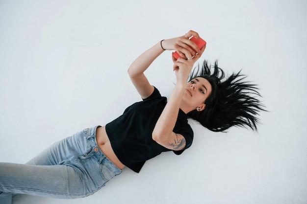Prendre Un Selfie. Une Jeune Adolescente Brune A Une Séance Photo En Studio Pendant La Journée Photo gratuit