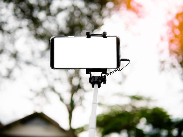 Prendre selfie par smartphone avec selfie bâton sur fond flou, montrant un écran blanc Photo Premium